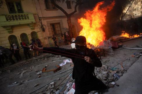 Manifestantes junto a barricadas incendiadas, en Santiago.