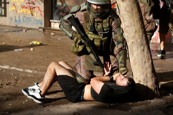 A policeman detains a demonstrators during a protest against Chile's...