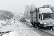 Varios vehículos circulan bajo la nieve en el municipio leonés de Riello.