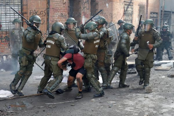 Police detain a demonstrator during a protest against Chile's...