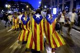 Varias jóvenes con banderas esteladas caminan por plaza de Catalunya.