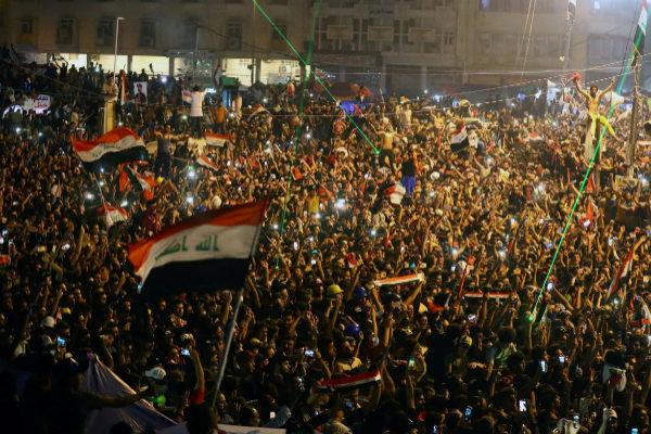 Iraqi demonstrators gathered at a Al- <HIT>Tahrir</HIT> square watch...
