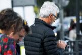 Transeúntes de la Gran Vía de Madrid usan sus móviles.