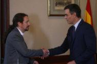 Pablo Iglesias y Pedro Sánchez se estrechan la mano en el Congreso tras acordar su pacto para gobernar.