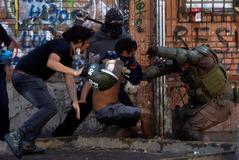 Manifestantes y policía antidisturbios se enfrentan durante una protesta en Santiago.
