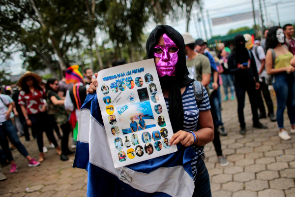 FILE PHOTO: A masked protester takes part in a protest against...