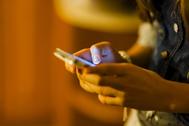 Una joven mira la pantalla de su teléfono móvil.