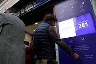 Una persona saca su turno en la administración de lotería Doña Manolita.