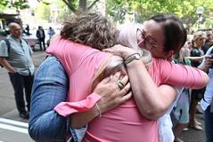 Afectadas por las mallas pélvicas se abrazan a la salida de la Corte Federal de Sydney.