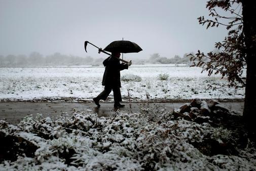 Un hombre camina por un camino nevado en el pueblo de O Cañizo, (A...