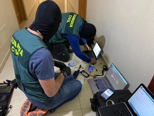 Dos agentes de la Guardia Civil requisan los aparatos encontrados, en...