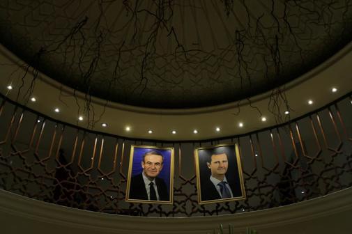 Los retratos de l presidente sirio Bashar Asad (dcha.) y su padre...