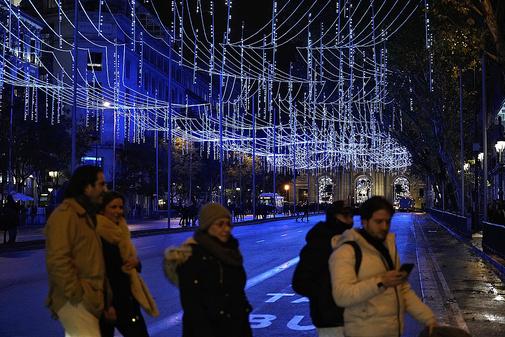 Ciudadanos pasean bajo las luces con la Puerta de Alcalá de fondo
