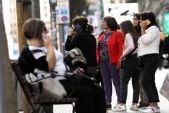 Varias personas utilizan sus teléfonos móviles en la Gran Vía de Madrid.