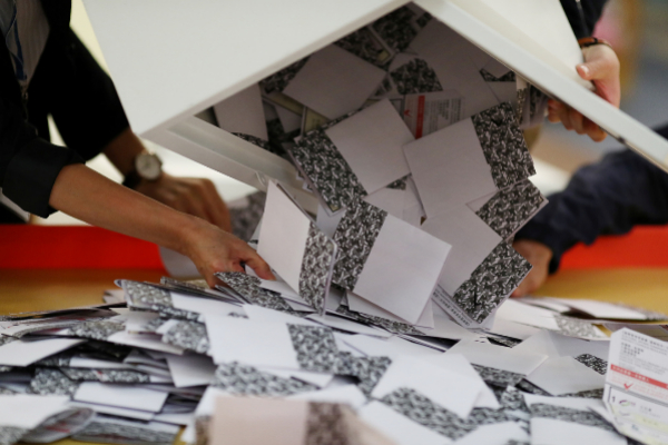 Officials open a ballot box at a polling station in Kowloon Tong,...