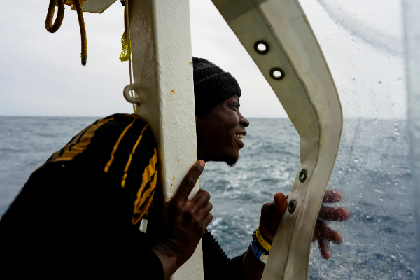 A migrant looks at the island of Sicily on board a NGO Proactiva...