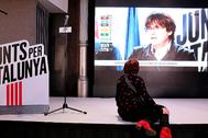 Una simpatizante de JxCat sigue, desde la sede del partido, el discurso de Puigdemont en la noche electoral.