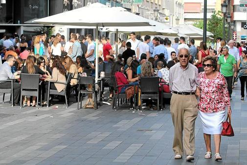 Dos vecinos pasean por la calle Castaños con las terrazas llenas de gente, en imagen de archivo. R. PÉREZ