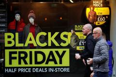 Un peatón pasa por delante de un comercio con el cartel del Black Friday