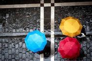 Tres personas se protegían de la lluvia con sus paraguas este sábado pasado en Pamplona, Navarra.