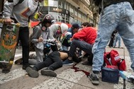 TOPSHOT - EDITORS NOTE: Graphic content / This image taken on November 23 ,2019 shows paramedics helping Dylan <HIT>Cruz</HIT> (18) after being hurt by a gas canister shot by a member city's anti-riot police (Esmad) during a protest in Bogota. - The young protester died November 25, 2019, after being injured by the public force on Saturday during protests against the government of Colombian President Ivan Duque. (Photo by Camila LASALLE RAMIREZ / AFP)