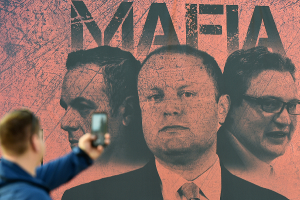 A man takes a photograph of a poster showing Malta's Prime Minister...