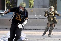 Un antidisturbio dispara una granada de gas contra un manifestante en las calles de Santiago.
