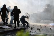 Un policía cae durante los choques callejeros con los manifestantes en Chile.