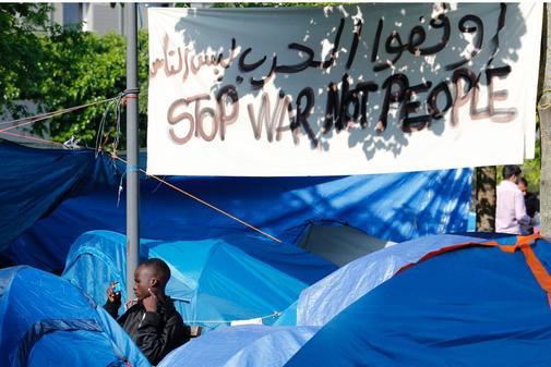 Migrantes en sus tiendas de campaña en un campamento improvisado en...