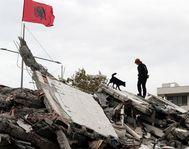 Los equipos de rescate colocan una bandera de Albania sobre los escombros que dejó el terremoto en Dürres.