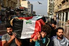Ciudadanos iraquíes portan un ataúd envuelto en una bandera del país, en Bagdad.