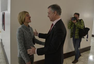 El lehendakari Iñigo Urkullu saluda a Pili Zabala durante un pleno anterior en los pasillos del Parlamento Vasco.