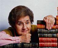 Retrato de Corín Tellado entre libros.