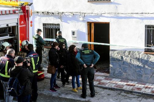 Agentes de bomberos y de la Guardia Civil investigan en una vivienda...