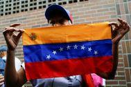 Una mujer sostiene la bandera bolivariana durante las elecciones generales del país.