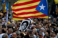 Varios manifestantes portan una bandera 'estelada' junto a una fotografía del expresidente de la Generalitat de Cataluña, Carles Puigdemont, en el segundo aniversario del 1-O.