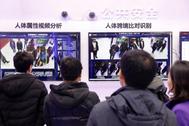 Varias personas miran sistemas de reconocimiento facial en un Congreso sobre el 5G en Pekín.