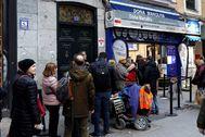 Varias personas hacen cola para comprar Lotería de Navidad