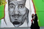 Mujeres saudíes caminan junto a un mural con la imagen del rey Salman, en Riad.