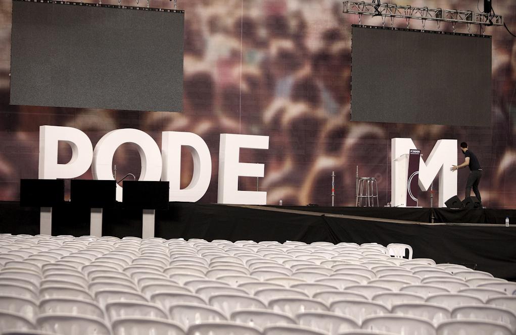 Un operario retira las letras de Podemos que decoraban el escenario de...