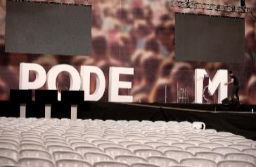 Un operario retira las letras de Podemos que decoraban el escenario de Vistalegre.