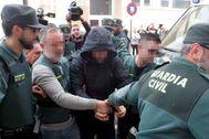 Jorge Ignacio, esposado y con capucha negra, escoltando por la Guardia Civil a la entrada del juzgado de Alzira.