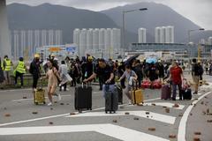 Pasajeros huyen a pie, con decenas de adoquines arrancados y esparcidos por el suelo, de una terminal del aeropuerto de Hong Kong en septiembre.