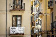 Cartel que denuncia la existencia de pisos turísticos ilegales en un edificio del barrio del Carmen de Valencia.
