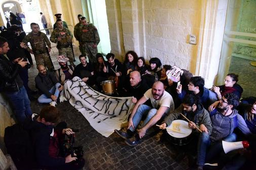 Activistas se sientan después de haber irrumpido en el edificio de la...