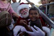 Papá Noel reparte regalos a migrantes, en Matamoros (México).