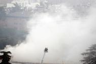 Los bomberos, ante la gran columna de humo provocada por el incendio.