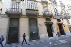 Dos viandantes pasan junto al local comercial ubicados en el edificio donde el PSOE de Málaga tiene una de sus sedes, en la calle Ollerías.