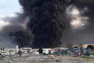 Enormes columnas de humo negro se elevan sobre una planta de reciclaje de residuos en Montornes del Vallès, en Barcelona.