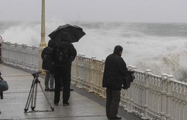 Varias personas observan el fuerte oleaje desde el paseo de La Concha en San Sebastián.